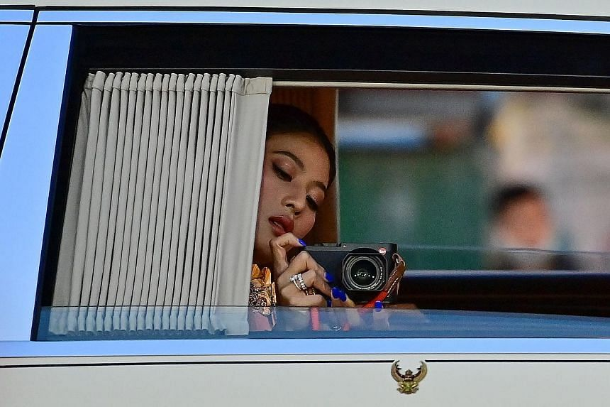 Princess Sirivannavari Nariratana taking a picture of royalist supporters on the way to the Grand Palace with her family for the Buddhist ceremony yesterday.