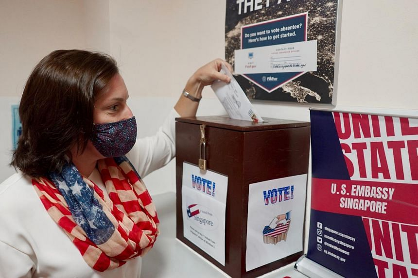 Voter Suzanne Murphy submits her ballot at the US Embassy in Singapore.