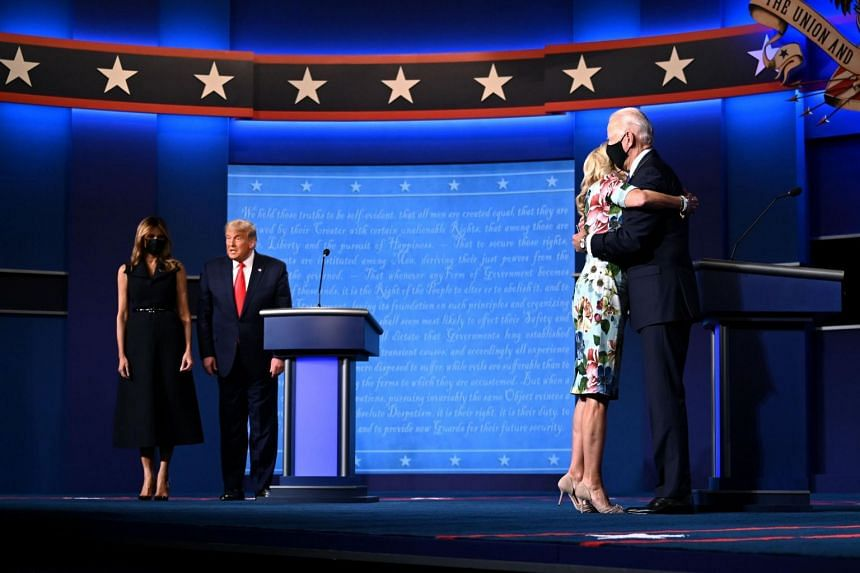 First Lady Melania Trump (left) stands with President Donald Trump as Jill Biden (right) hugs husband Democratic presidential candidate Joe Biden after the final presidential debate in Nashville on Oct 22, 2020.