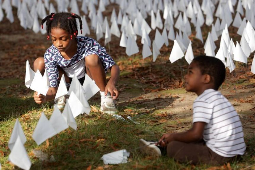 Hope Larkin plants flags with her brother during a press preview of the In America How Could This Happen art project in Washington, DC, on Oct 23, 2020.