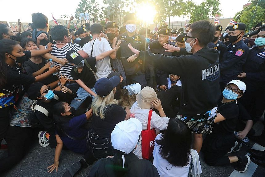 Police scuffling with anti-government demonstrators near a royal motorcade carrying Thailand's Queen Suthida and Prince Dipangkorn, in front of Government House on Oct 14, the 47th anniversary of the 1973 student uprising, in Bangkok.