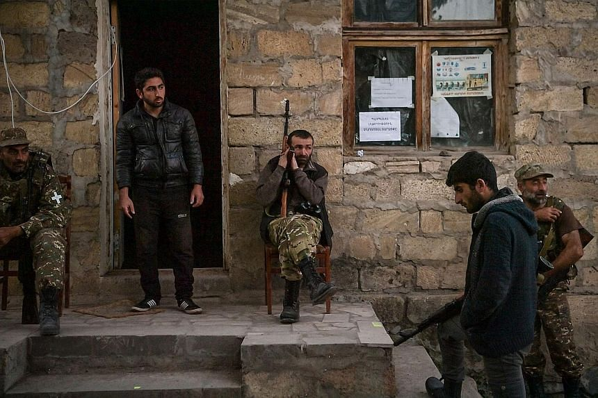 Volunteer fighters at a village south-east of Stepanakert in Nagorno-Karabakh on Friday. Local officials accused Azerbaijan's forces of firing missiles into residential buildings in Stepanakert, the largest city in the region, which Baku denied. Azer