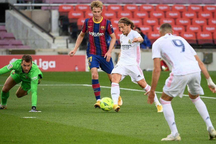 Real midfielder Luka Modric shooting to score against Barcelona at the Nou Camp on Oct 24 to seal the visitors' 3-1 win.