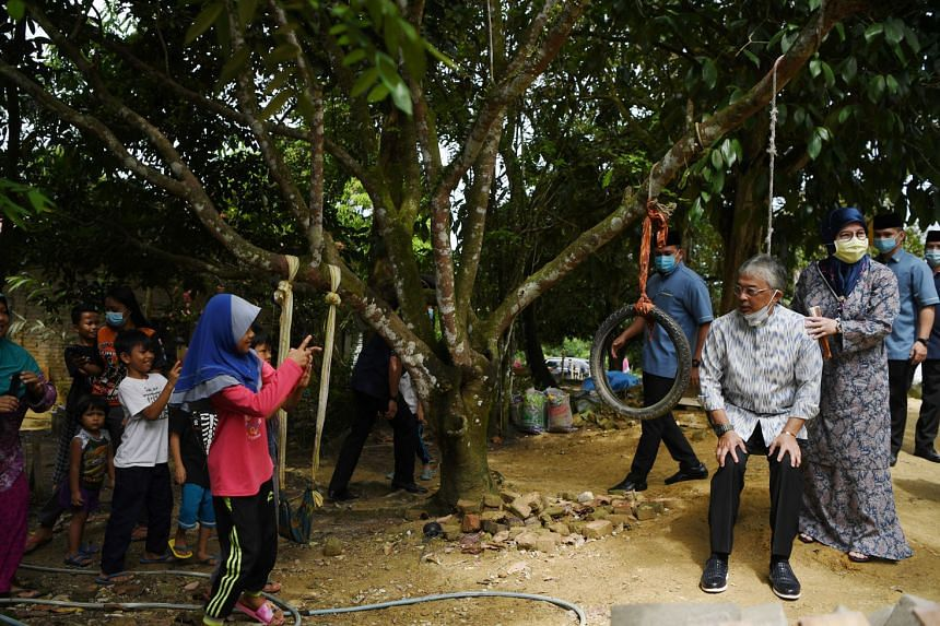 Sultan Abdullah and his wife, Tunku Azizah Aminah Maimunah Iskandariah, with villagers in Pahang in June. With Malaysia's ethnic Malay community divided like never before, the King is being dragged into the fray to play the central role of adjudicato