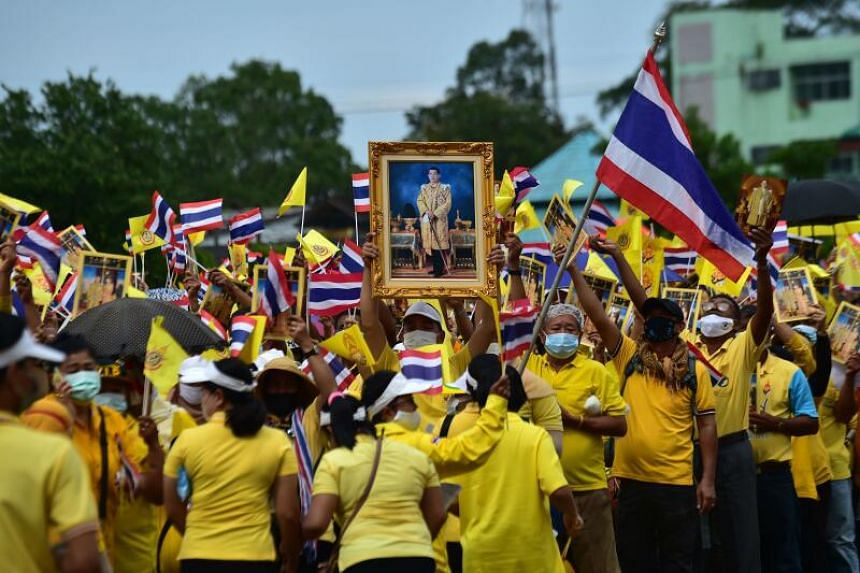 Thai royalist supporters waving flags and displaying a portrait of King Maha Vajiralongkorn at a rally to show support for the royal establishment in Narathiwat, Thailand, on Oct 25, 2020.