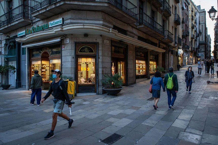Residents walk past La Colmena bakery in downtown Barcelona, Oct 26, 2020.