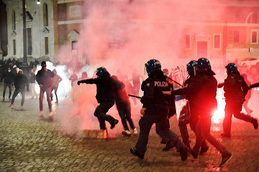 Italian police officers (above) clashing with far right Forza Nuova party activists in Rome's Piazza del Popolo during a protest last Saturday against the government's measures to curb the spread of Covid-19. Workers (below) piling up chairs at a bar