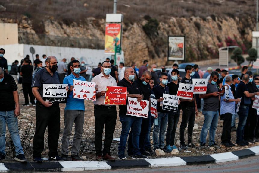 Demonstrators hold up signs as they protest at Umm-Al Fahem, Israel on Oct 25, 2020.