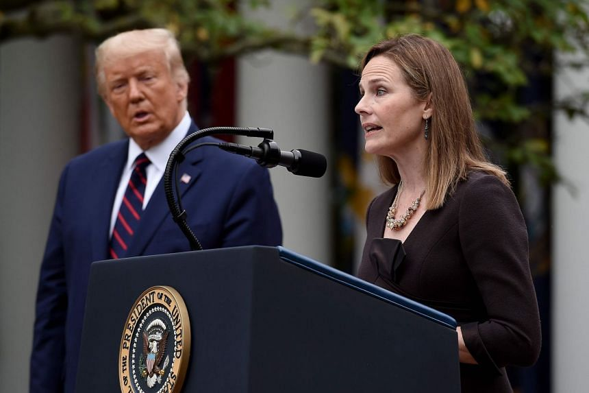 A September 2020 photo shows Barrett speaking after being nominated to the US Supreme Court by Trump (left).
