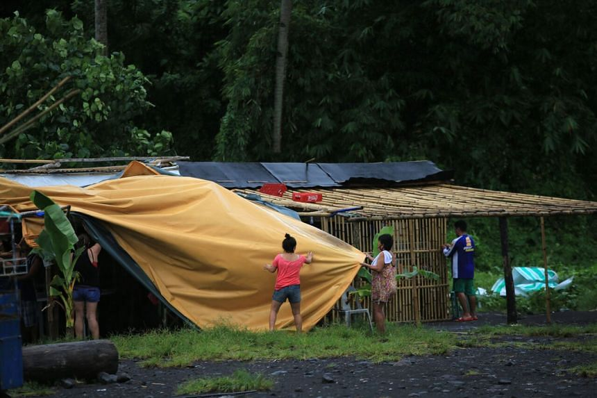 Residents fix a tarp over a house ahead of Typhoon Molave's landfall along the coastal area of Legaspi City, south of Manila, on Oct 25, 2020.