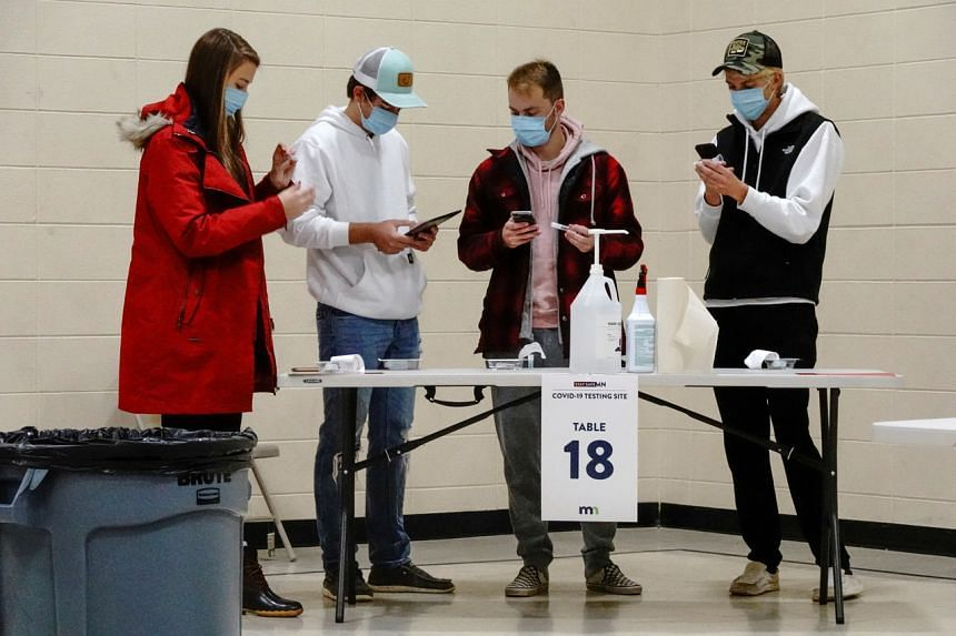 North Dakota residents prepare to self-administer Covid-19 saliva tests at a testing site in Minnesota on Oct 25, 2020.