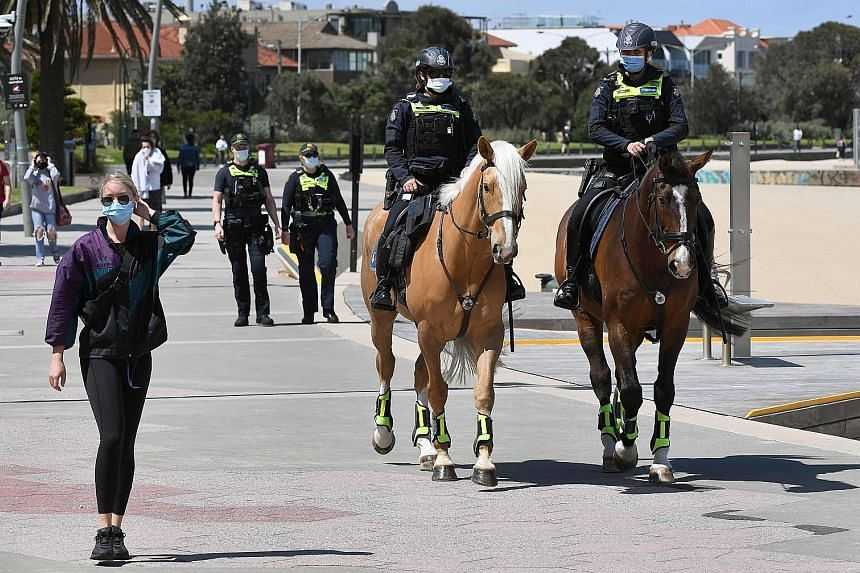 A police patrol in Melbourne's St Kilda Esplanade yesterday. Stay-at-home orders for Melbourne residents will be lifted from midnight today. Restaurants, beauty salons and retail stores will also be permitted to reopen. The move comes after the city