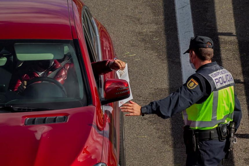 A driver shows a safe-conduct document to a police officer at a checkpoint in Asturias, Spain, on Oct 26, 2020.