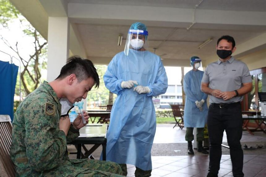 Senior Minister of State for Defence Zaqy Mohamad (right) observing a saliva collection trial at the Infantry Training Institute at Jurong Camp II.