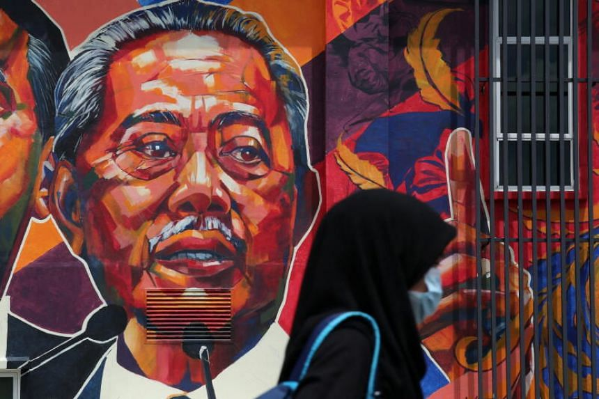 A woman passes by a mural depicting Malaysia's Prime Minister Muhyiddin Yassin in Kuala Lumpur, Malaysia Oct 27, 2020.