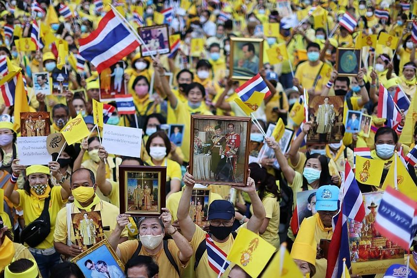 Royalists wearing yellow shirts at an event to support the monarchy in Bangkok on Tuesday. One of them held up a picture of the late King Bhumibol Adulyadej. PHOTO: REUTERS Pro-democracy demonstrators showing the three-finger anti-government salute d