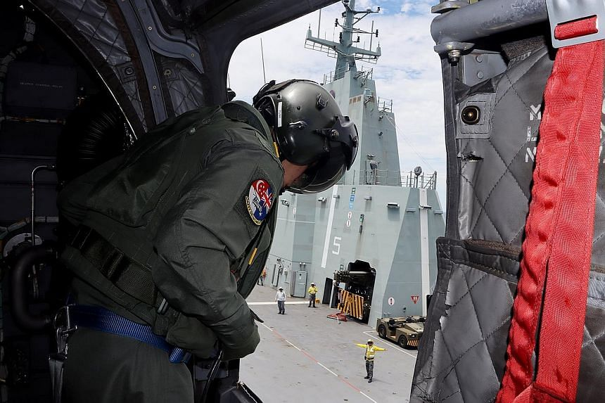 A Republic of Singapore Air Force air crew specialist (left) on board the CH-47D Chinook keeping a lookout for blind spots during the helicopter's landing on the HMAS Adelaide (above) in the waters off Townsville in Queensland, Australia, last Saturd