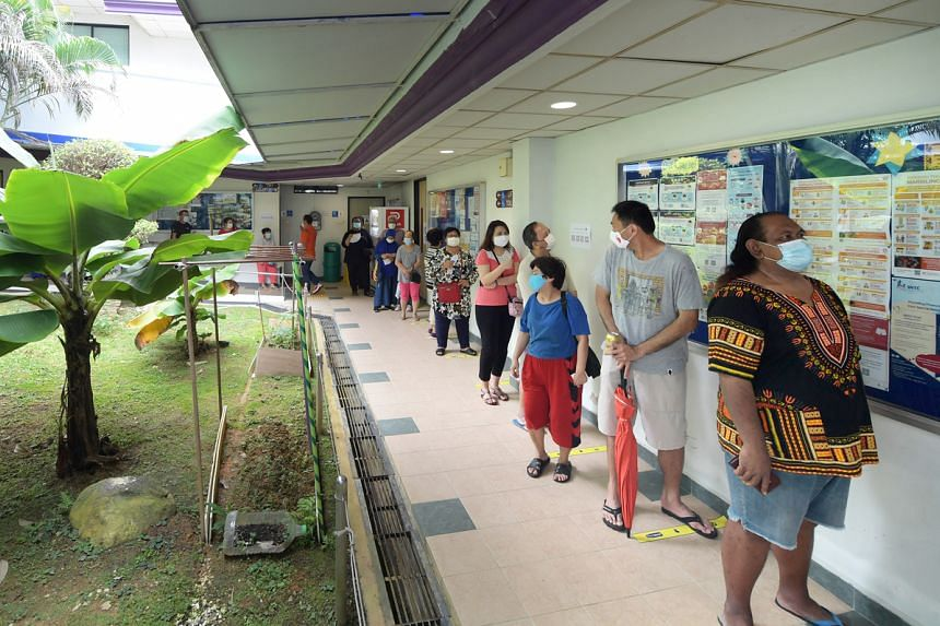 Residents in Marsiling queue to collect their TraceTogether tokens at the Marsiling Community Centre on Oct 29, 2020.