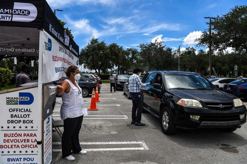 Poll workers help a voter put their ballot in a drive- thru ballot drop box in Miami on Aug 18, 2020.