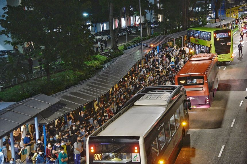 Crowds waiting at the bus stop outside Queenstown MRT station after a power fault disrupted train services, on Oct 14, 2020.