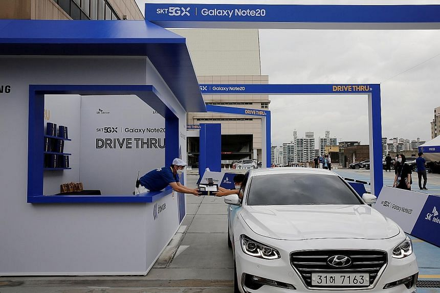A visitor collecting a Samsung Galaxy Note 20 smartphone during a driving-through event for purchasers in Seoul on Aug 13. Sales of Samsung smartphones jumped nearly 50 per cent during the September quarter as the roll-out of its latest Galaxy Note s