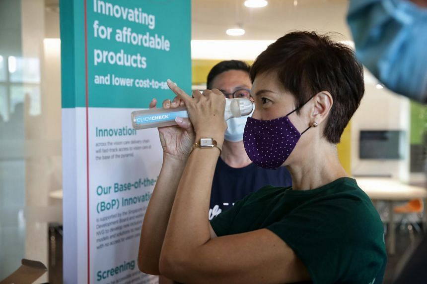 Manpower Minister Mrs Josephine Teo trying out ClickCheck during the launch of Essilor's three-year migrant workers vision care programme on Oct 30, 2020.