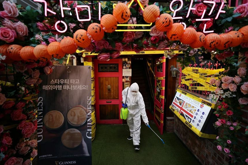 A worker spraying disinfectant along a street in Itaewon, a major nightlife district in Seoul, on Oct 29, 2020.