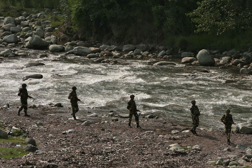 A photo taken in August 2013 shows Indian Border Security Force soldiers patrolling near the Line of Control.