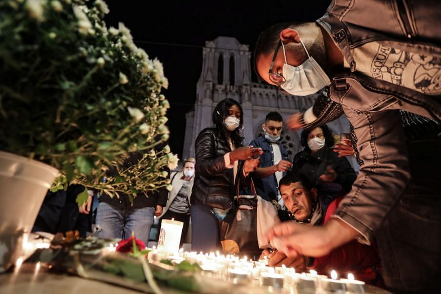 People light candles outside the basilica in Nice in tribute to the three victims of a knife attacker.