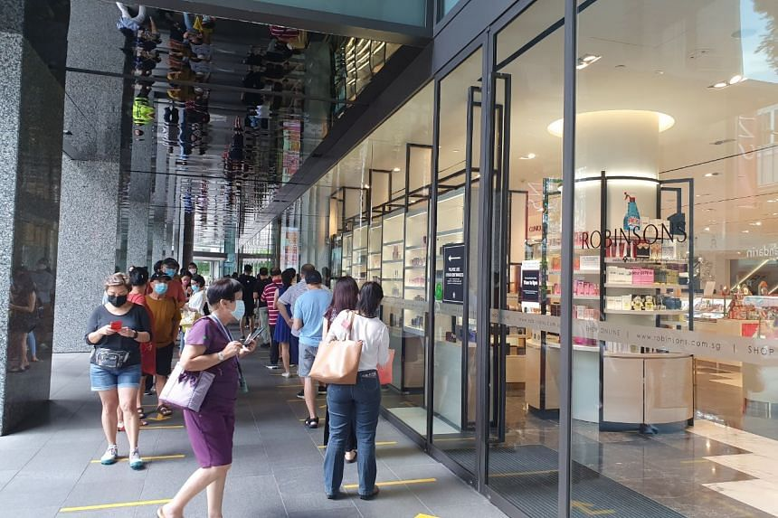 Shoppers queue outside the Robinsons store at The Heeren on Oct 30, 2020.