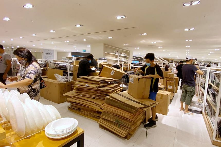 Workers at the Robinsons store in Raffles City packing items from shelves into carton boxes on Oct 30, 3030.