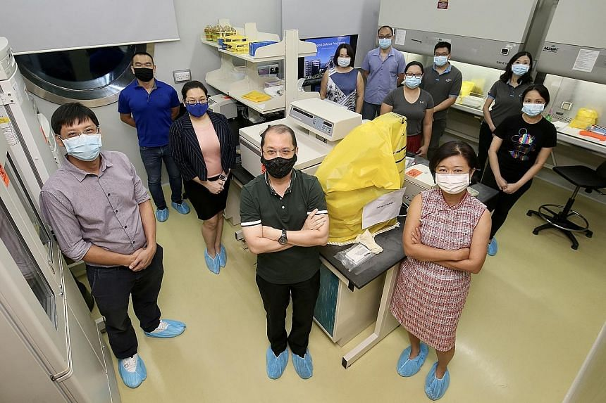 Associate Professor Tan Boon Huan (front row, right), director of DSO National Laboratories' biological defence programme, with members of her winning team at a DSO lab in Kent Ridge. She said her team's role in the national Covid-19 effort was the r