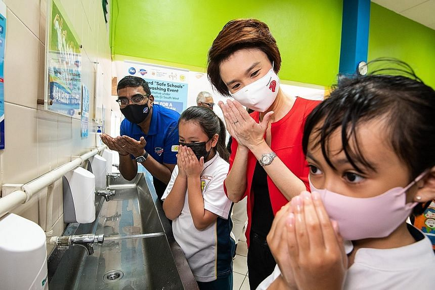 Mayor of South West District Low Yen Ling participating in a hand-washing demonstration on Thursday with pupils from Lianhua Primary School. With them is Mr Shankar Viswanathan, Procter & Gamble (P&G) senior vice-president for Malaysia, Singapore and