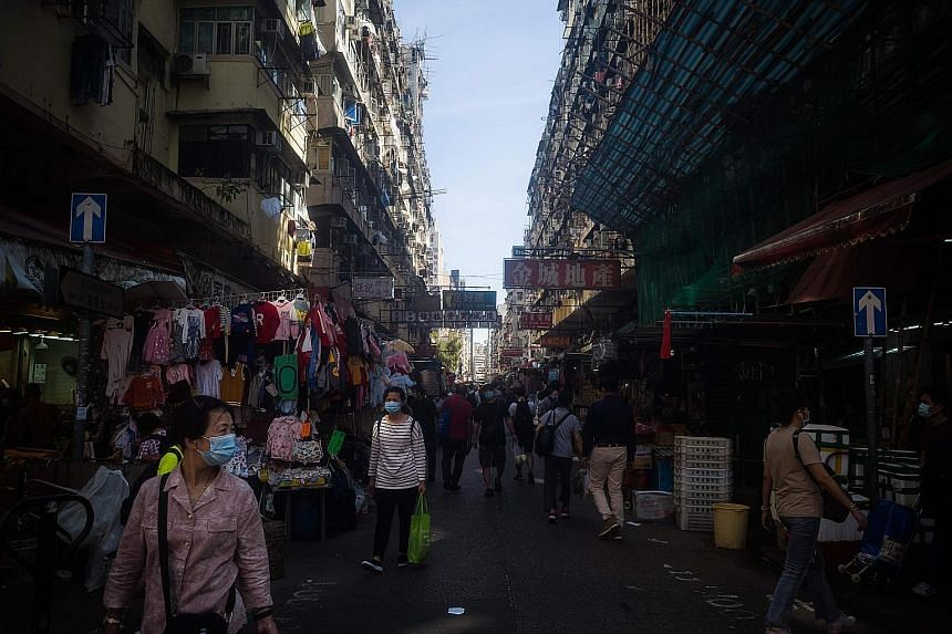 "People in a street market in Hong Kong on Tuesday. Financial Secretary Paul Chan said if the flow of people and commerce between Hong Kong and mainland China is safely restored, the city can be ""revitalised substantially"" even if the global economy r"