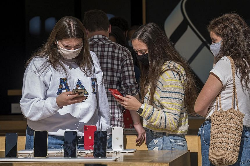 People checking out the new iPhones at an Apple store in San Francisco earlier this month. Apple has reported quarterly results that topped Wall Street estimates after record sales of Macs and services made up for a delayed iPhone 12 launch. But its