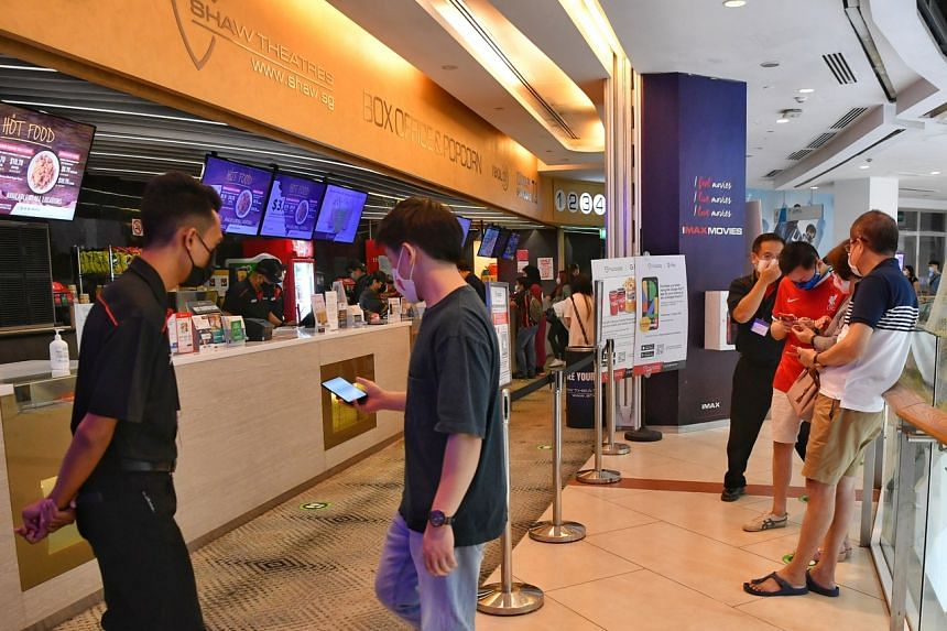 Moviegoers show their TraceTogether check-in before entering the Shaw Theatre at Jcube on Oct 31, 2020.