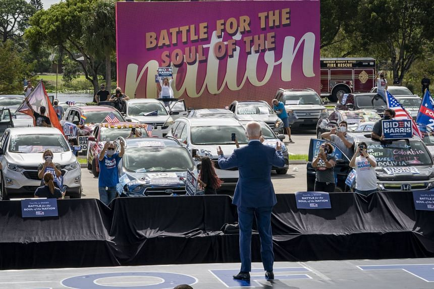 "Democratic presidential candidate Joe Biden on stage at a ""drive-in"" campaign rally in Coconut Creek, Florida, on Thursday. Attendees remained in or near their cars to avoid the possible spread of Covid-19. They were also required to wear masks, but"