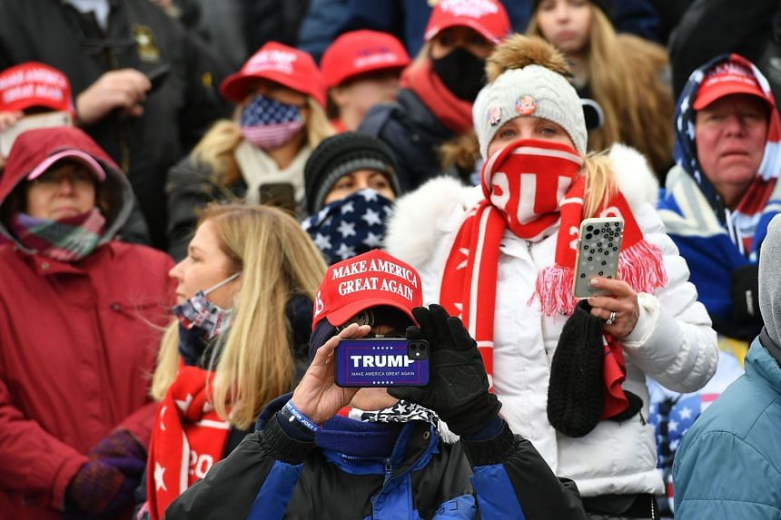 Supporters listen as US President Donald Trump speaks at a rally in Michigan, on Oct 30, 2020.