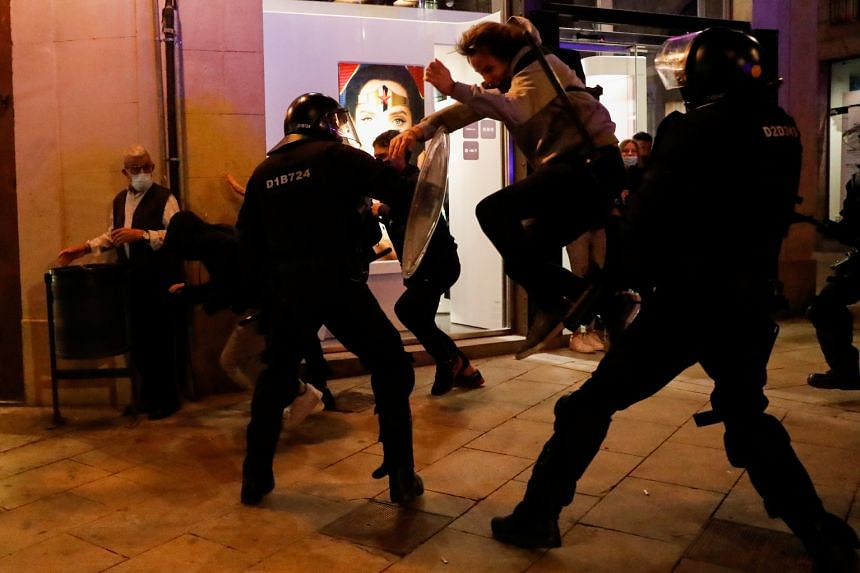 Demonstrators clash with police officers during a protest against virus restrictions in Barcelona, on Oct 30, 2020.