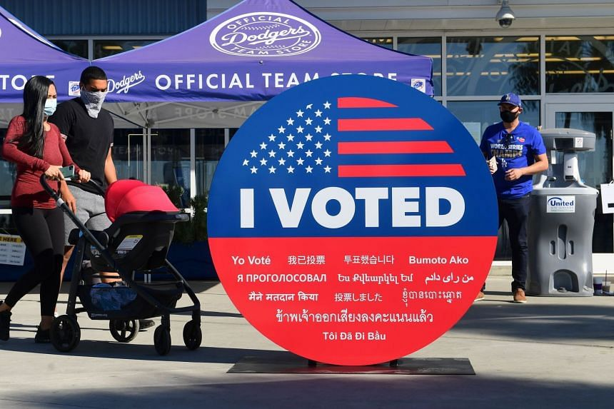 "People walk past a large ""I Voted"" display as early voting for the election begins in Los Angeles, on Oct 30, 2020."