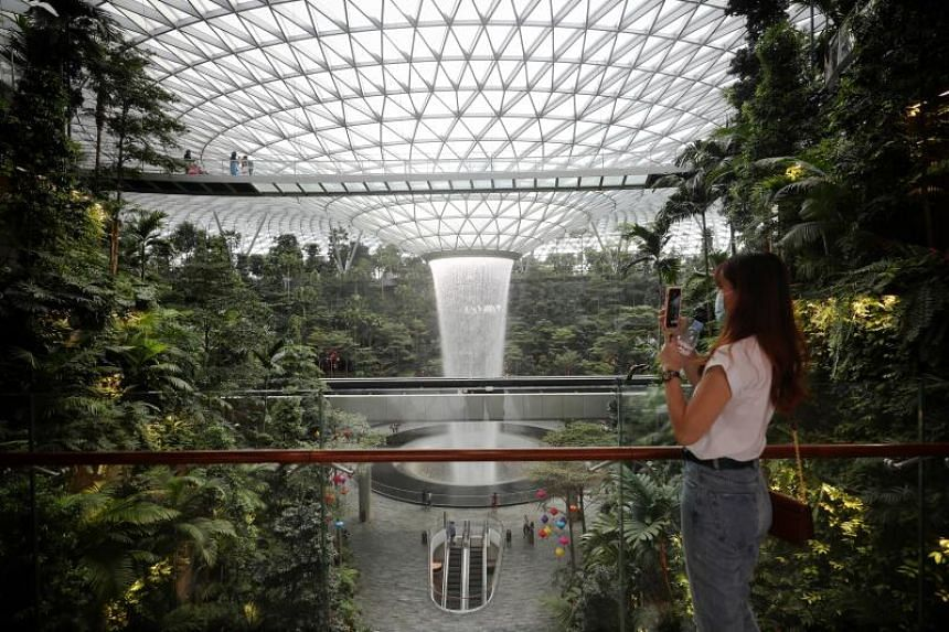 A visitor takes photos of the rain vortex at Jewel Changi Airport on Oct 14, 2020.
