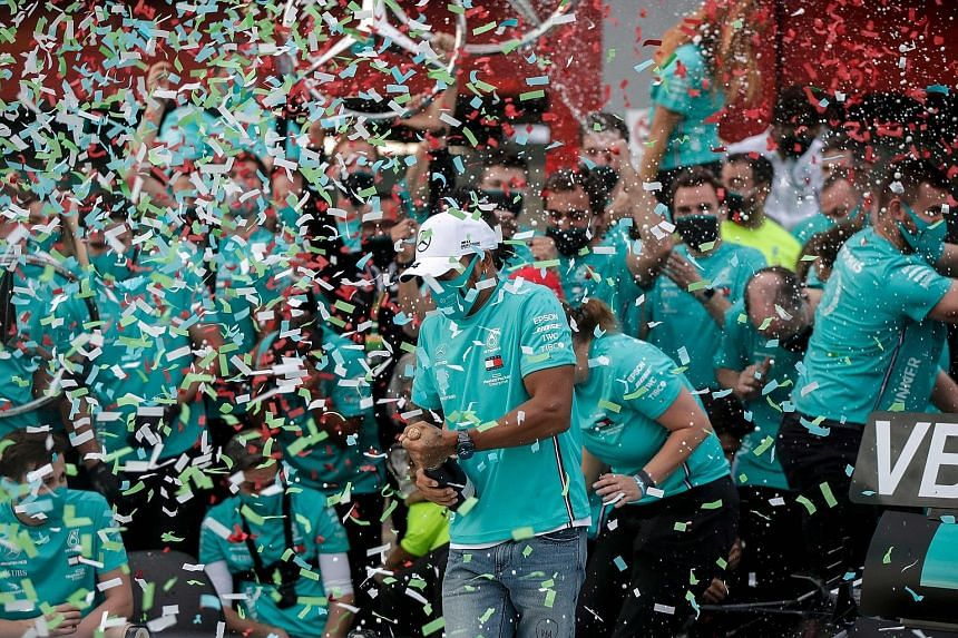 Above: Lewis Hamilton and his team celebrating in the pits after Mercedes won their seventh straight F1 constructors' title at Imola on Sunday. Left: Hamilton and team principal Toto Wolff in high spirits.