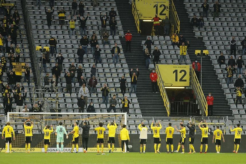 """Dortmund players acknowledging their fans in the Signal Iduna Park's famed """"Yellow Wall"""", which held a fraction of its 25,000 capacity when the team played Freiburg last month."""