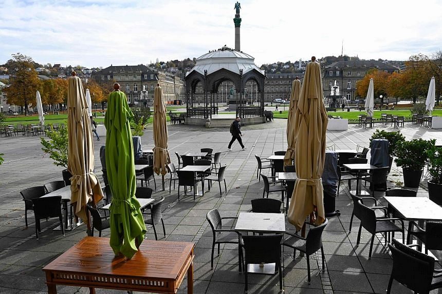 An empty outdoor dining area in Stuttgart, Germany, yesterday. Chancellor Angela Merkel has ordered a round of shutdowns from yesterday until the end of the month, during which bars, cafes, restaurants, theatres, operas and cinemas must close. Tighte