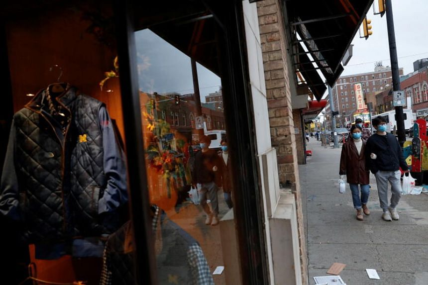 People wearing face masks walk past a clothing store in Oct 26, 2020, at the University of Michigan campus, where state health officials in Michigan issued a stay-in-place order for undergraduate students.