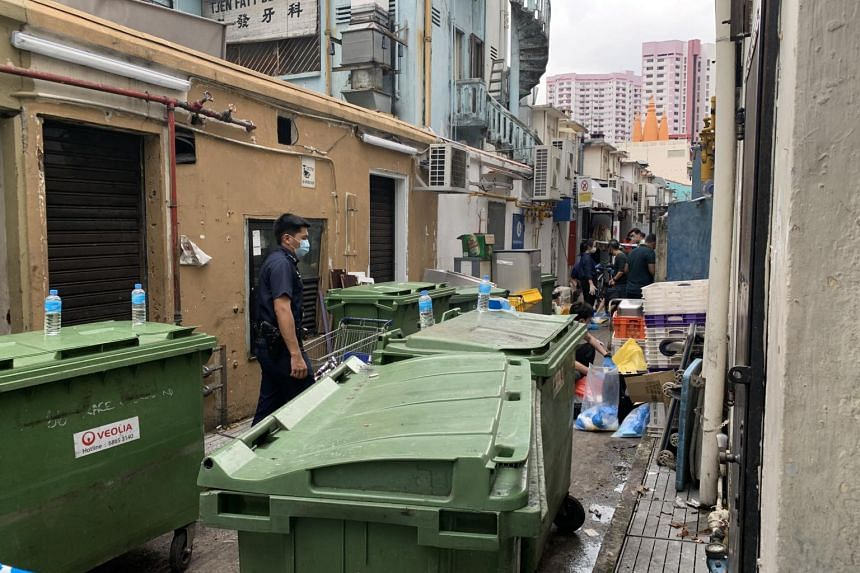 Police officers at an alleyway behind the Anjappar Chettinad Restaurant at Little India, where the body of a man in his late 40s was found.
