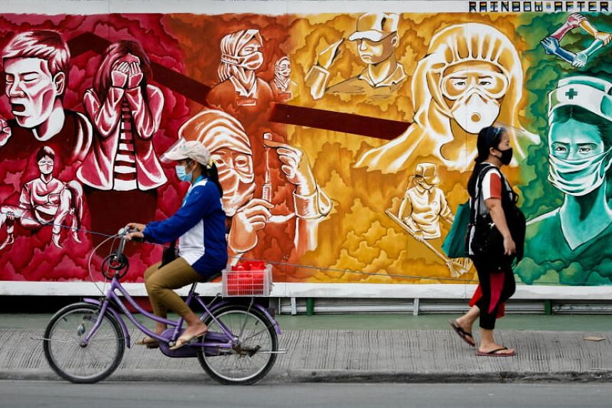 People pass a mural dedicated to healthcare workers, in Pasig City, Metro Manila, on Oct 30, 2020.