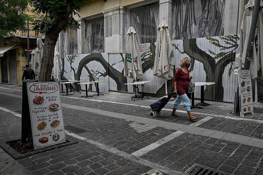 Empty tables and chairs on the terraces of two restaurants in downtown Vienna yesterday, the first day of a new lockdown in the country. Austria's cases in recent weeks have surged well past the levels recorded in spring, forcing the government to im