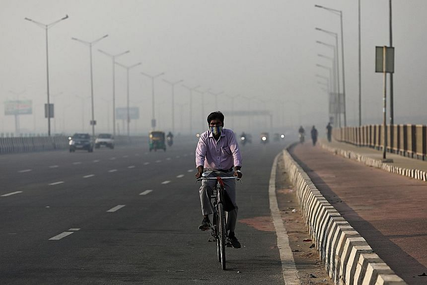 A masked cyclist riding along a highway on a smoggy morning in New Delhi last Friday. Coronavirus cases and air pollution are spiking across major cities in India, including New Delhi, one of the worst-affected areas for smog from rural burning. PHOT