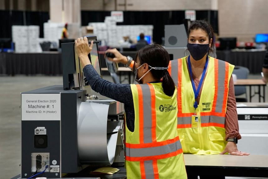 Electoral workers clean a ballot counting machine during the 2020 US presidential election in Philadelphia, Pennsylvania, US.